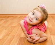 Den roliga liten flicka ligger på ett hus däckar Royaltyfri Bild