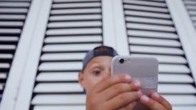 Den roliga gulliga pysen spelar lekar på smartphonen Pysen av 5-6 år gamla håll ringer för nästan hans framsida arkivfilmer
