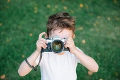 Den roliga gulliga ungen önskar att ta en bild med hans tappningfilmkamera Arkivfoto