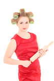 Den roliga hemmafrun med rulle-klämmer fast och papiljotter över vit Fotografering för Bildbyråer
