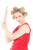 Den roliga hemmafrun med rulle-klämmer fast och papiljotter Royaltyfri Bild