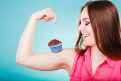 Den roliga kvinnan rymmer chokladkakan på armen Royaltyfri Foto