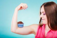 Den roliga kvinnan rymmer chokladkakan på armen Arkivbild