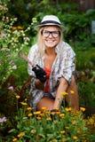 Den roliga landsflickan tar omsorg av henne blommor Arkivfoton