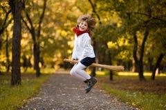 Den roliga lilla flickan flyger på kvasten i höst royaltyfri fotografi