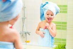 Den roliga lilla flickan gör ren tänder med tandborsten i badrum royaltyfria foton
