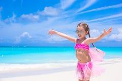 Den roliga lilla flickan har gyckel på strandsommarsemester Fotografering för Bildbyråer