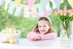 Den roliga lilla flickan i kanin gå i ax med påskägg Arkivbild
