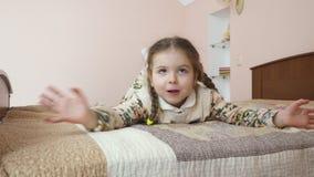 Den roliga lilla flickan lägger på säng hemma lager videofilmer