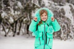 Den roliga lilla flickan som har gyckel i härlig vinter, parkerar royaltyfria bilder