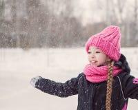 Den roliga lilla flickan som har gyckel i härlig vinter, parkerar under snöfall Royaltyfri Fotografi