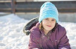 Den roliga lilla flickan som har gyckel i härlig vinter, parkerar under snöfall Fotografering för Bildbyråer