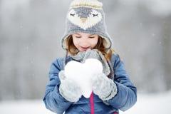 Den roliga lilla flickan som har gyckel i vinter, parkerar Royaltyfri Bild