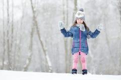 Den roliga lilla flickan som har gyckel i vinter, parkerar Arkivbild