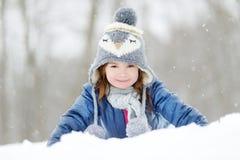 Den roliga lilla flickan som har gyckel i vinter, parkerar Arkivfoto