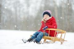 Den roliga lilla flickan som har gyckel med en släde i härlig vinter, parkerar Gulligt barn som spelar i en snö royaltyfri foto