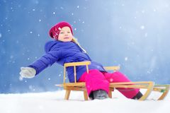 Den roliga lilla flickan som har gyckel med en sleight i härlig vinter, parkerar Royaltyfria Foton