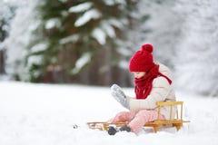 Den roliga lilla flickan som har gyckel med en sleight i härlig vinter, parkerar Arkivfoton