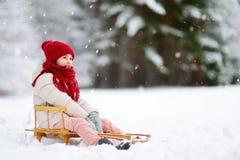 Den roliga lilla flickan som har gyckel med en sleight i härlig vinter, parkerar Royaltyfri Foto