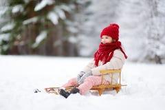 Den roliga lilla flickan som har gyckel med en sleight i härlig vinter, parkerar Royaltyfria Bilder