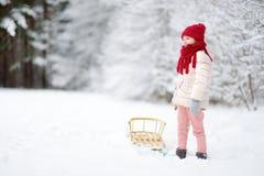 Den roliga lilla flickan som har gyckel med en sleight i härlig vinter, parkerar Fotografering för Bildbyråer