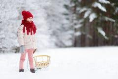 Den roliga lilla flickan som har gyckel med en sleight i härlig vinter, parkerar Royaltyfri Fotografi