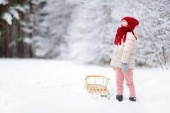Den roliga lilla flickan som har gyckel med en sleight i härlig vinter, parkerar Royaltyfri Bild