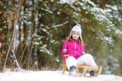 Den roliga lilla flickan som har gyckel med en sleight i vinter, parkerar Arkivbilder