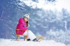 Den roliga lilla flickan som har gyckel med en sleight i vinter, parkerar Royaltyfri Bild