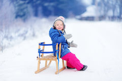 Den roliga lilla flickan som har gyckel med en sleight i vinter, parkerar Fotografering för Bildbyråer