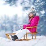 Den roliga lilla flickan som har gyckel med en sleight i vinter, parkerar Royaltyfri Foto