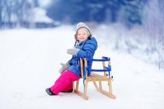 Den roliga lilla flickan som har gyckel med en sleight i vinter, parkerar Royaltyfria Bilder