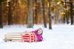 Den roliga lilla flickan som har gyckel med en sleight i vinter, parkerar Royaltyfria Foton