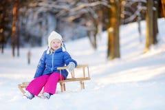 Den roliga lilla flickan som har gyckel med en sleight i vinter, parkerar Arkivfoto