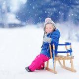 Den roliga lilla flickan som har gyckel med en sleight i vinter, parkerar Arkivfoton