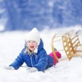 Den roliga lilla flickan som har gyckel med en sleight i vinter, parkerar Royaltyfri Fotografi