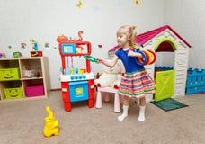 Den roliga lilla flickan som kastar plast-, ringer på leksakelefant arkivbild