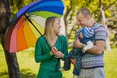 Den roliga lyckliga familjen plaing i parkera Arkivfoto