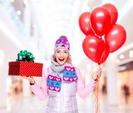 Den roliga lyckliga kvinnan med den röda gåvaasken och ballonger på shoppar Arkivfoto