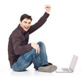 Den roliga manen med den lyftta bärbar dator räcker upp Fotografering för Bildbyråer