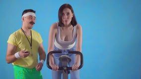 Den roliga manlagledaren från 80-tal med mustaschen och exponeringsglas undersöker en ung kvinna på motionscykelen långsam mo stock video