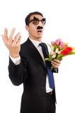 Den roliga mannen med blommor som isoleras på vit Royaltyfri Foto