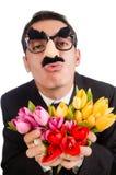 Den roliga mannen med blommor som isoleras på vit Royaltyfria Foton