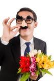 Den roliga mannen med blommor som isoleras på vit Fotografering för Bildbyråer