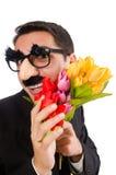 Den roliga mannen med blommor som isoleras på vit Royaltyfri Fotografi
