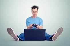 Den roliga mannen med en styrspak sitter på golvet framme av en bärbar dator Gamerlekar Royaltyfri Bild