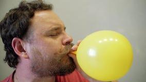 Den roliga mannen med ett skägg och en mustasch blåser upp en gul ballong med hans mun stock video