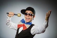Den roliga mannen med mic i karaokebegrepp Royaltyfri Foto