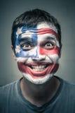 Den roliga mannen med USA-flaggan målade på framsida Royaltyfri Fotografi