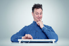 Den roliga mannen tänker klickar på skriva inknappen eller inte Obeslutsam programmerare Arkivfoto